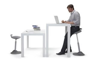 hier sieht man wie der muvman-new passend für sitzen am tisch in normaler sitzhöhe und als stehhilfe am stehtisch an maschinen beim bügeln an empfangstheken und reparaturannahme ergonomische stehhilfe ist